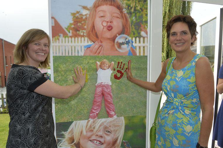 Burgemeester Tinne Rombouts en Chantal Van Overveld openen de opvoedingswinkel met een handafdruk.