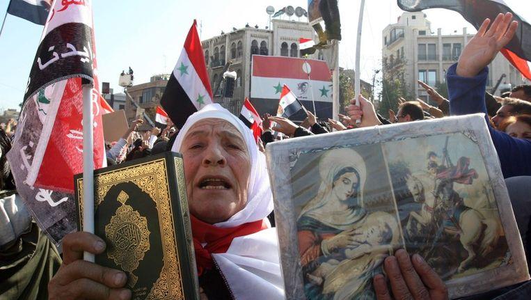 Syrische christenen houden religieuze afbeeldingen omhoog om te laten zien dat ze president Assad steunen. Beeld afp