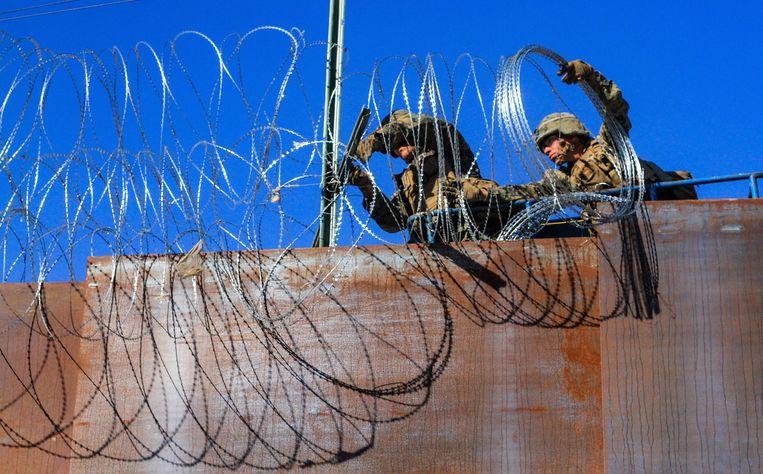 Militairen verstevigen de grens in Tijuana met prikkeldraad.