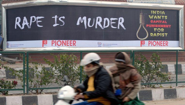 Vrouwen rijden op een scooter langs een billboard met daarop de tekst 'verkrachting is moord', in New Delhi Beeld AFP