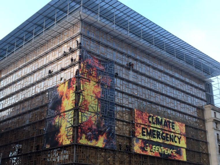 Spandoeken van Greenpeace donderdagochtend op het Europa-gebouw in Brussel. Beeld Marc Peeperkorn