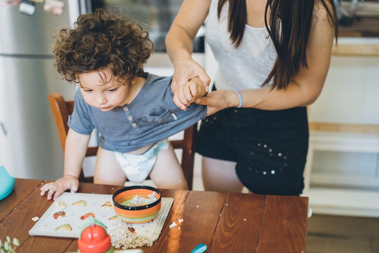 Mother undressed the t-shirt to her baby boy after lunch