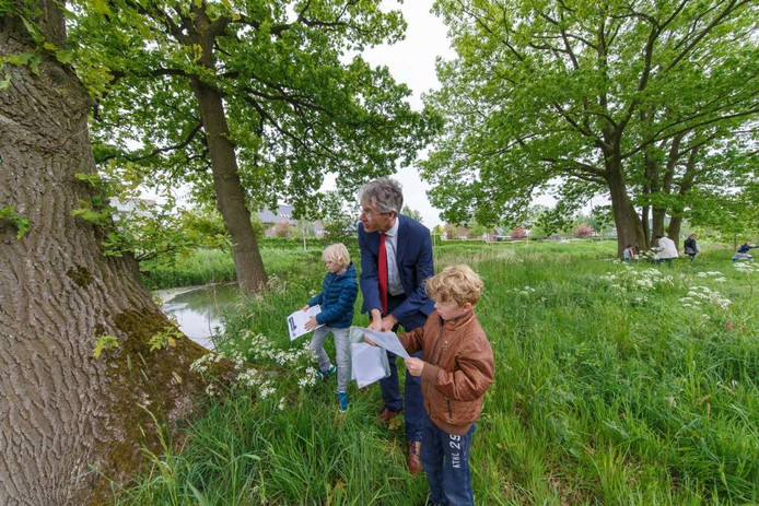 HCO-baas Arie Slob kijkt met kinderen uit groep 3 van De Wendakker naar oude eiken die er al waren voor Stadshagen in de jaren negentig ontwikkeld werd.
