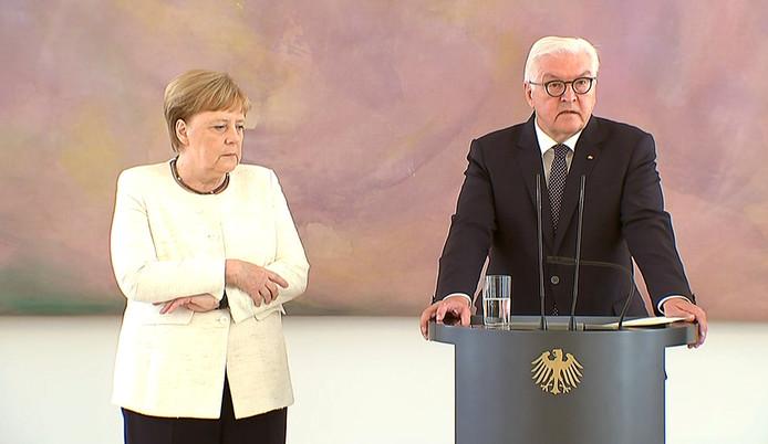 De Duitse bondskanselier Angela Merkel (links) en president Frank-Walter Steinmeier tijdens de ceremonie. Merkel houdt haar handen op een gegeven moment tijdens het praatje stevig tegen zich aangedrukt.