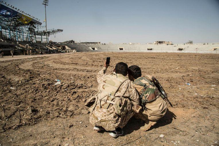 Strijders van de SDF nemen een selfie in het stadion van Raqqa, nadat de stad veroverd is op IS. Beeld null