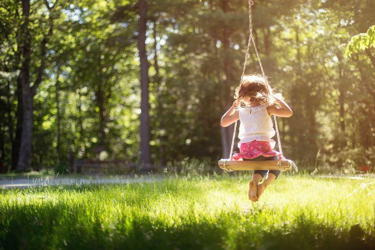 Girl sitting on swing in field