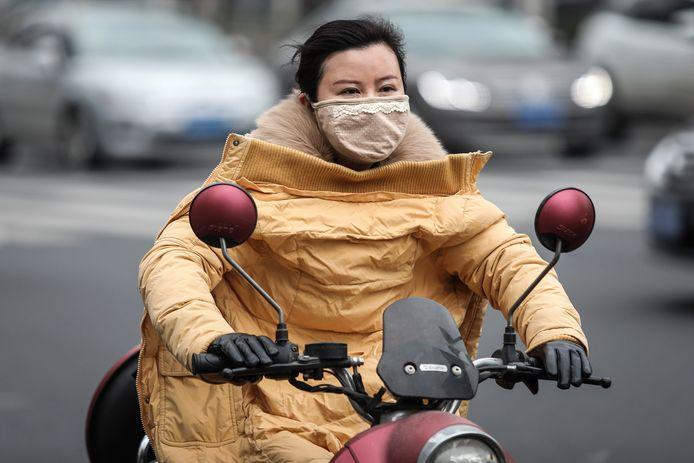 Het straatbeeld in Wuhan vult zich met mensen met een masker voor de mond. Zij dragen het uit angst voor een mogelijke besmetting met het corona-virus. (Foto Getty Images)