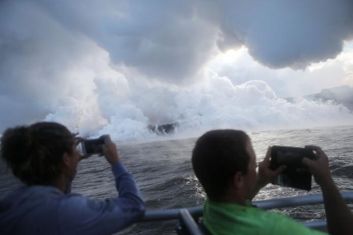 Met veel gesis en geknetter ontwikkelen zich grote stoomwolken als de lava uit de vulkaan Kilauea op Hawaii de zee bereikt. Foto Mario Tama