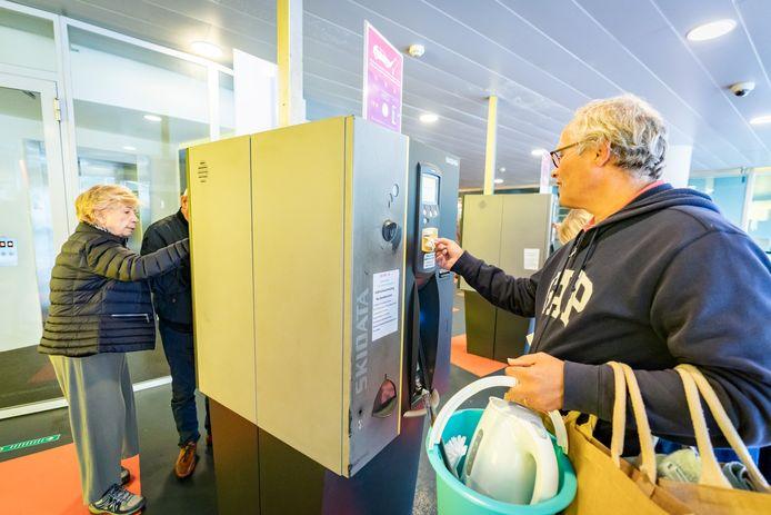 Bezoekers van Cityplaza betalen bij een parkeerautomaat.