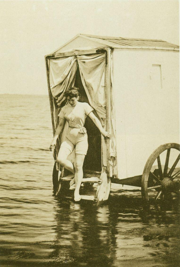 Een jonge vrouw stapt uit een badkoets. Beeld