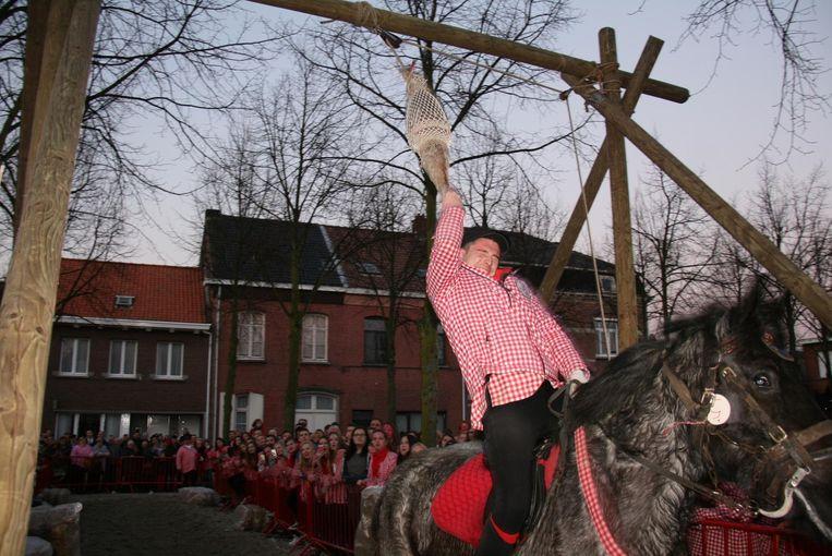 Duidelijk niet voor watjes: al rijdend op een paard moet je de nek van een dode gans proberen af te trekken.