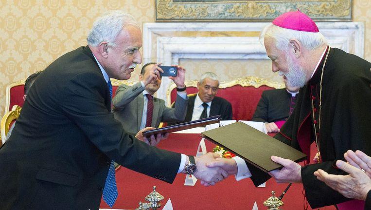 Aartsbisschop Paul Richard Gallagher (r) en de Palestijnse minister van Buitenlandse Zaken Riad al-Malki bezegelen het verdrag met een handdruk. Beeld afp