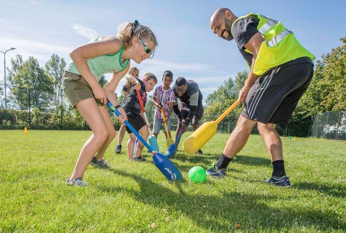 Kinderen uit de buurt vermaken zich met een potje knotshockey.