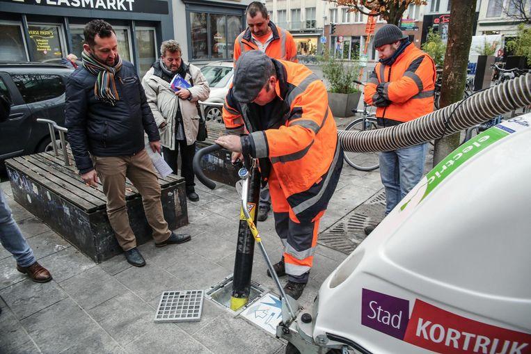 Stadsarbeiders komen de asbakken in de grond geregeld ledigen.