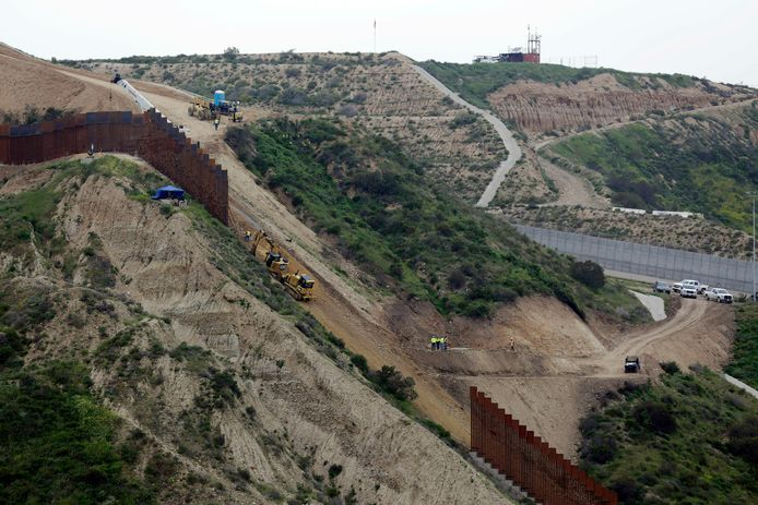 Werken aan de grensmuur tussen San Diego (rechtsboven) en Tijuana in Mexico (linksonder).