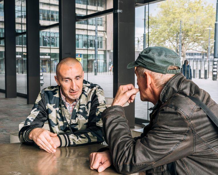 Szymon praat met Leszek, ervaringsdeskundige bij stichting Barka.  Beeld Rebecca Fertinel