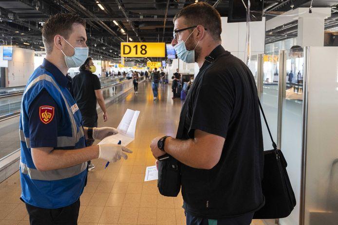 Medewerkers van de GGD ondervragen reizigers op luchthaven Schiphol.