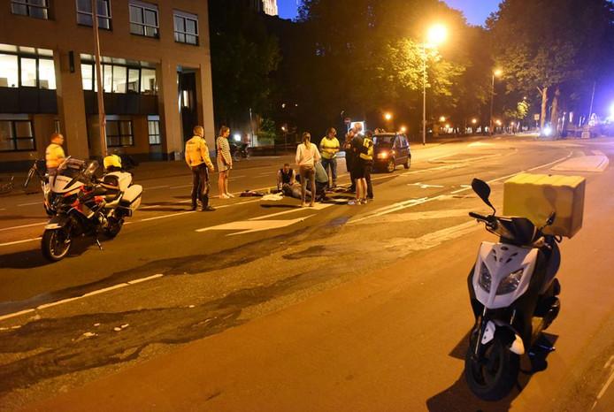 Omstanders verleenden de gewonde scooterrijder eerste hulp op de Catharijnesingel.