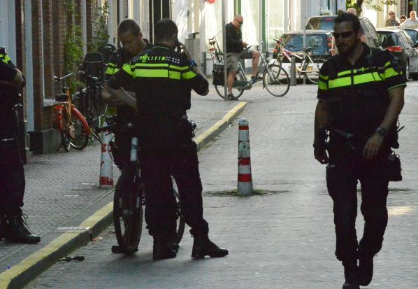 Agenten houden in de Herderstraat in Den Haag de wacht bij een wapen dat weggegooid is tijdens een vlucht voor de politie.