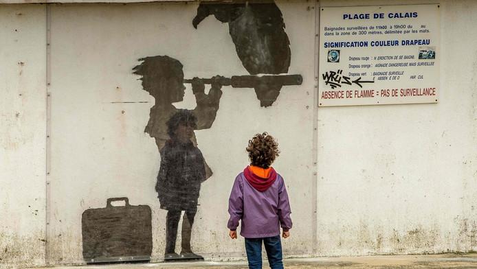 Op het strand van Calais liet Banksy eind vorig jaar dit kunstwerk achter: een kind met een koffer dat door een telescoop kijkt, waar een gier op zit.