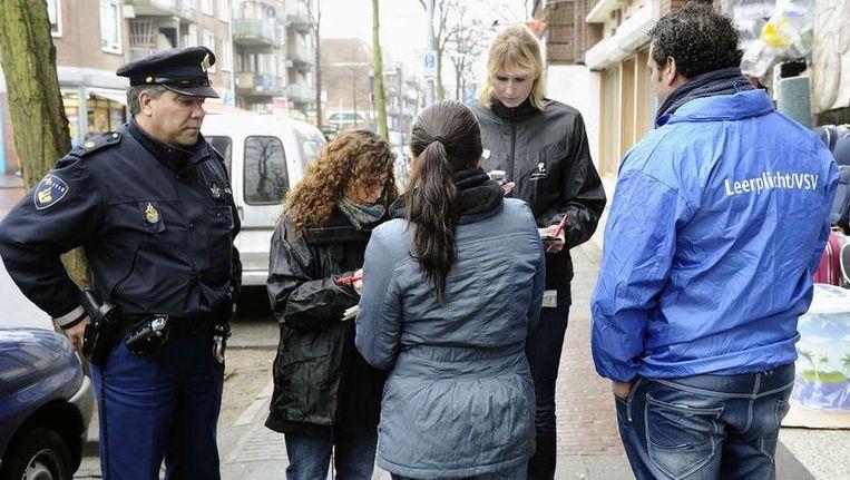 Leerplichtambtenaren en politieagenten controleren in Den Haag. Beeld ANP