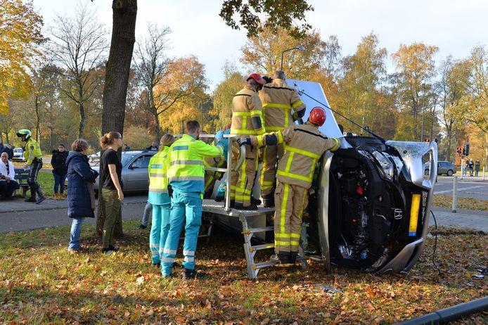 De brandweer haalt een slachtoffer uit de auto na een ongeval op het kruispunt van de Laan van Zevenhuizen met de Mheenlaan in Apeldoorn.