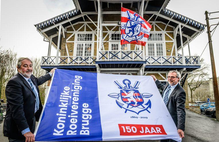 Marc D'hondt en Hubert De Witte met de nieuwe clubvlag aan hun geklasseerde clublokaal.