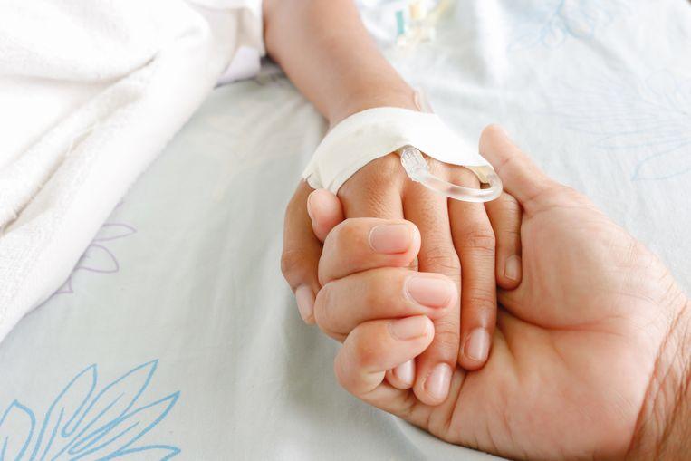 Een moeder houdt het handje van haar zieke kind vast.
