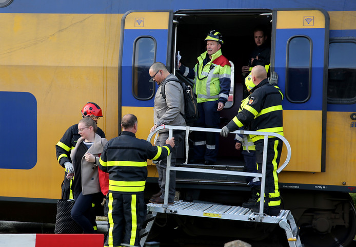 Reizigers worden uit de ontspoorde trein gehaald,  na de botsing van de vrachtwagen bij Wouw