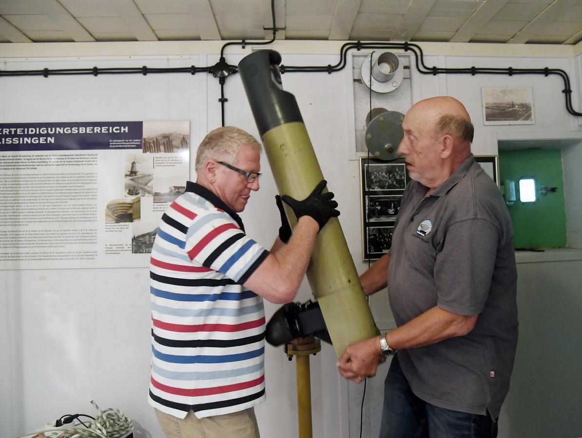 Kees van Klinken (links) en Henk Meijer halen de periscoop uit zijn dagelijkse behuizing, een vitrine in de museumbunker in Vlissingen.