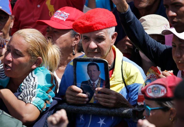 Een aanhanger van de 'Bolivariaanse revolutie' houdt een portret op van voormalig president Hugo Chávez tijdens de toespraak van zijn opvolger Maduro. Het was zaterdag twintig jaar geleden dat Chávez aan de macht kwam in Venezuela. Beeld AP