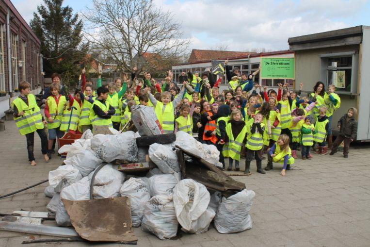 De leerlingen van basisschool De Sterrebloem verzamelen bij hun buit na de inzameling van het zwerfvuil. Ze raapten 57 zakken afval bij elkaar.