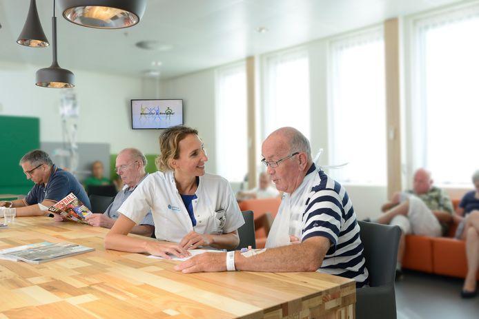 Cardioloog Inge Wijnbergen spreekt in de hartlounge een patiënt die zojuist is gedotterd. Deze foto werd voor de uitbraak van corona gemaakt.