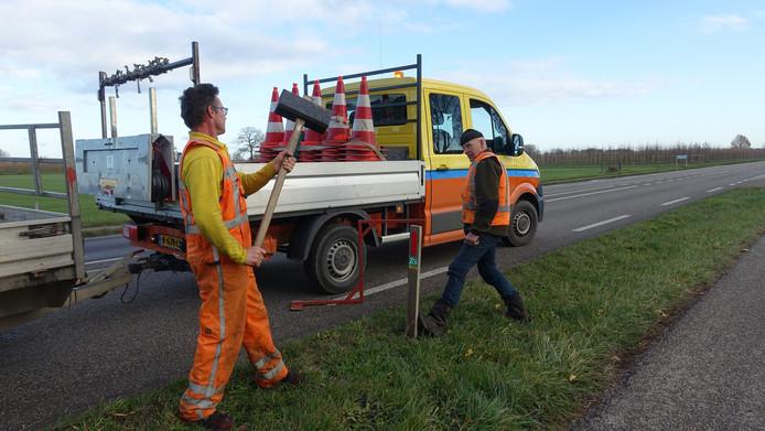Medewerkers van de provincie Gelderland plaatsen duurzame  reflectorpaaltjes tussen Elst en Randwijk.