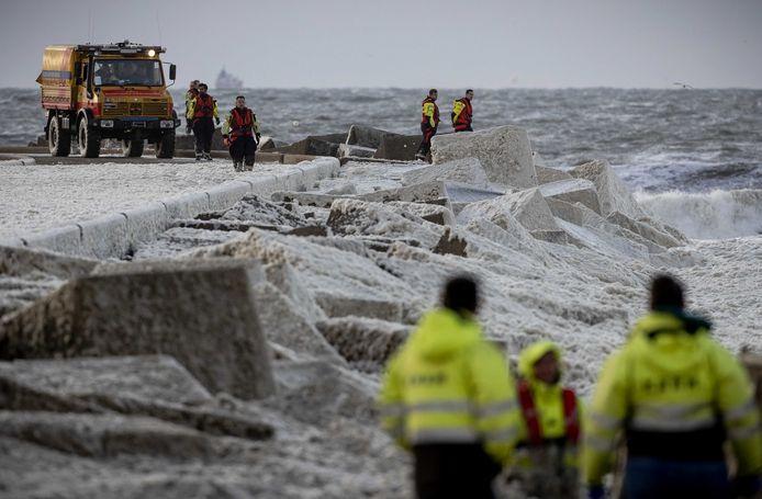 Medewerkers van de KNRM zoeken naar een groep surfers die bij het Noordelijk Havenhoofd bij de kustplaats in problemen is gekomen.