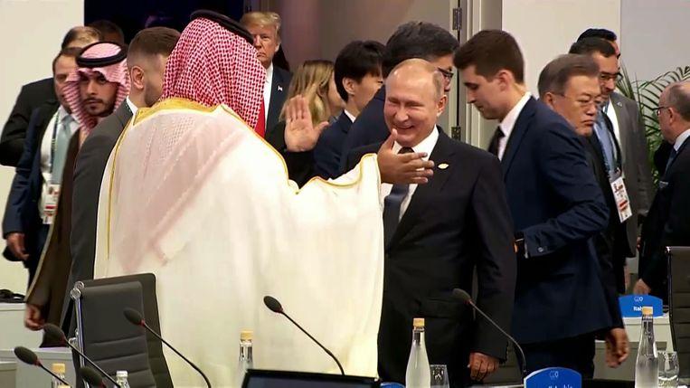 De Saoedische kroonprins Bin Salman v (links) en Vladimir Poetin (rechts) groeten elkaar hartelijk tijdens de G20 top in Buenos Aires.  Beeld AFP