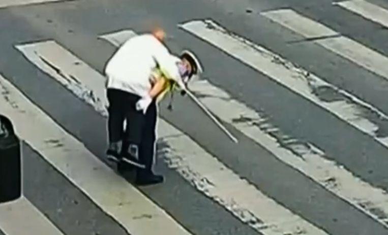 Geen tijd om trage oude man te laten oversteken: agent neemt man op de rug en brengt hem naar overkant