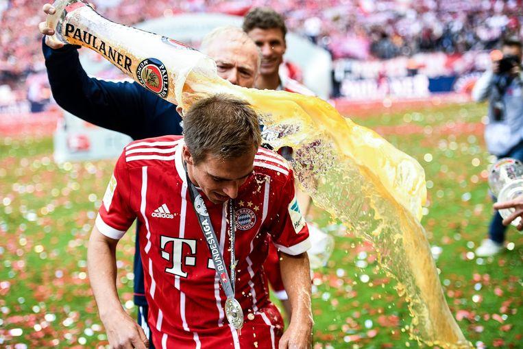 Philipp Lahm krijft een bierdouche bij Bayern.  Beeld EPA