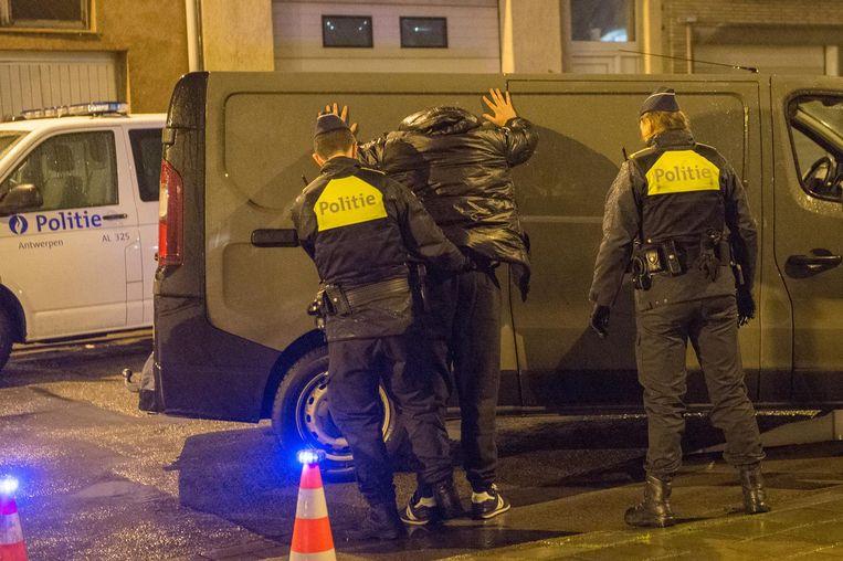 Politieagenten controleren een man op drugs- en wapenbezit.