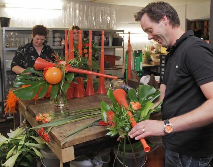 Samen met zijn 'meiden' Esther (links) en Lisa is Harold Reuser druk in de weer om vuvuzela's in bloemstukjes te verwerken. foto Peter van Huijkelom