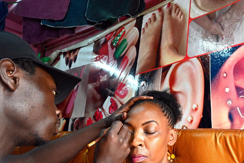 De Keniaanse visagist Silver Wambua biedt zijn diensten aan bij het busstation van Nairobi.