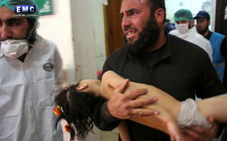 Een man draagt een kind binnen bij een provisorisch ziekenhuis in de Syrische stad Khan Sheikhoun, in de noordelijke regio Idlib. Deze foto is verspreid door activisten van de anti-regeringsgroep Edlib Media Center. Beeld AP
