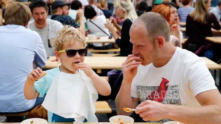 Een man en een jongen genieten van een gratis maaltijd tijdens Damn Food Waste, afgelopen zondag in Rotterdam Beeld epa