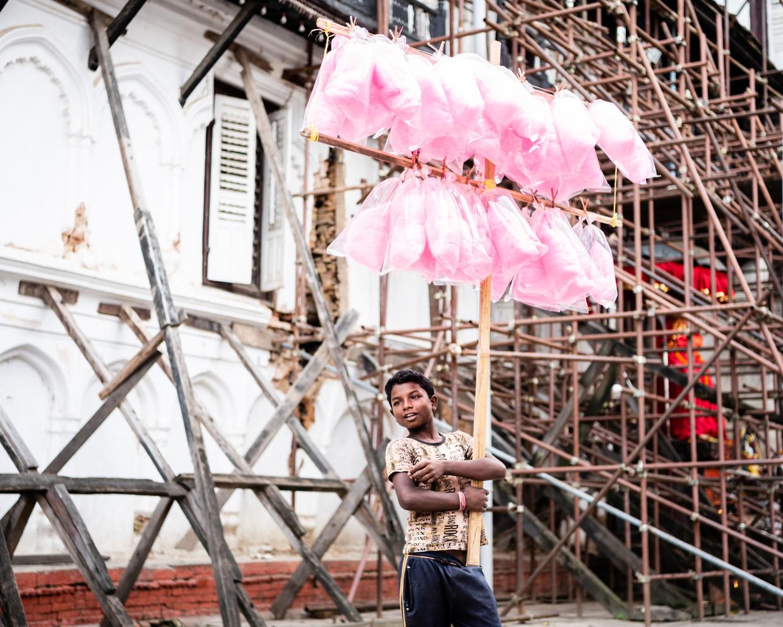 Een jongen verkoopt op Durbar Square in Kathmandu zakken met suikerspin. Veel tempels en paleizen op het plein staan in de steigers.  Beeld Katja Poelwijk