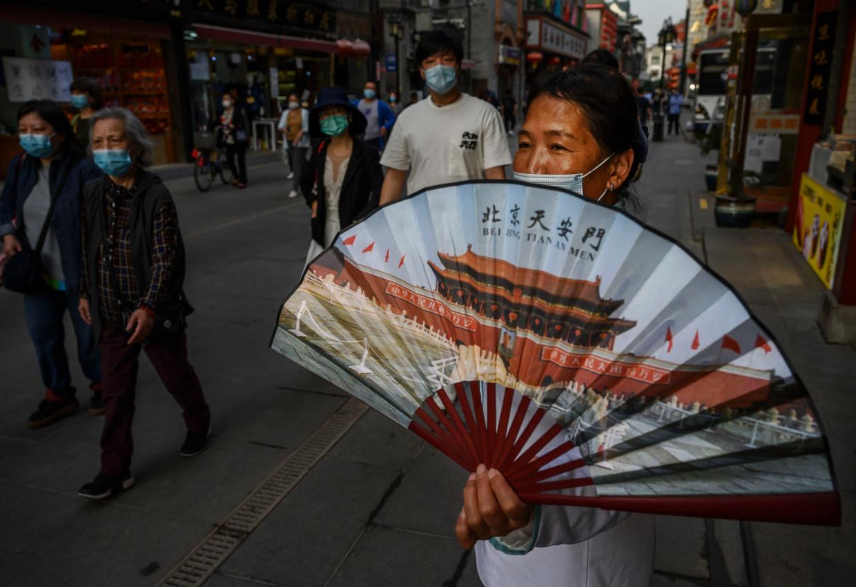 Een medewerker van een restaurant in Beijing probeert klanten te lokken met een waaier.  Beeld Getty