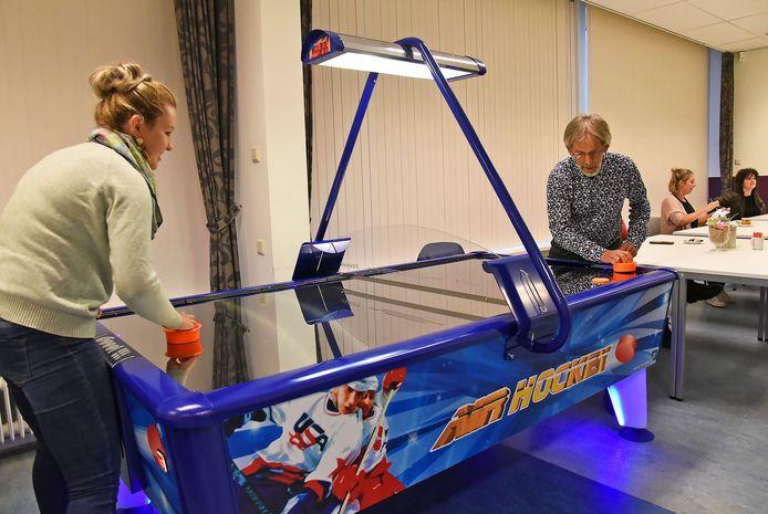 Voorzitter Robert Asselman speelt een partijtje airhockey met vrijwilligster Carmen Smedema.