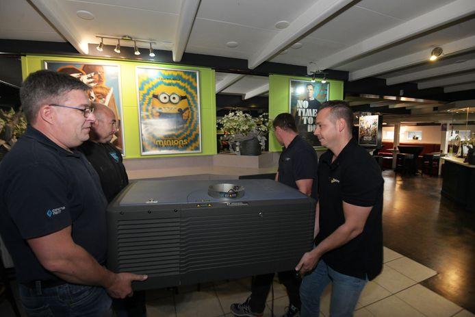 Specialisten hebben één van de projectoren van Cinema Tiel ontmanteld en brengen die naar de centrale hal van de bioscoop.
