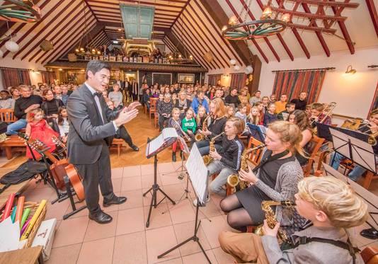 Wim Steenbakker dirigeert het jeugdorkest EMM-Advendo tijdens de Kerst Muziekavond in Klein Stelle.