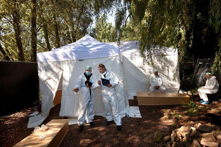 September 2010: werknemers van het NFI staan bij een tent op de begraafplaats St. Barbara. Zij gaan het dna van onbekende lijken vergelijken met materiaal in hun dna-databank. Beeld Guus Dubbelman / de Volkskrant
