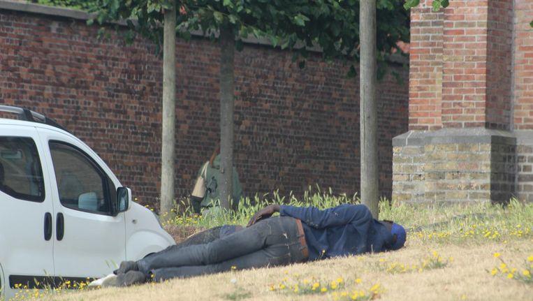 Twee mannen doen een dutje aan de Sint-Donaaskerk.